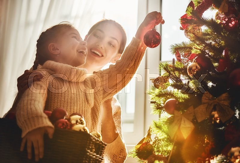 Merry Christmas and Happy Holidays! Mom and daughter decorate the Christmas tree indoors. The morning before Xmas. Portrait loving family close up, stock photo