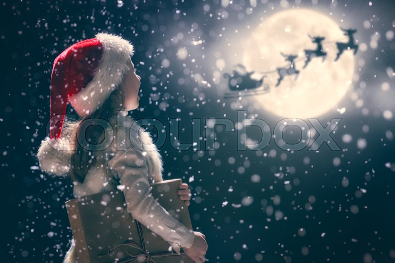Merry Christmas and happy holidays! Cute little child girl with xmas present. Santa Claus flying in his sleigh against moon sky. Kid enjoy the holiday. Portrait kid with gift on dark background, stock photo