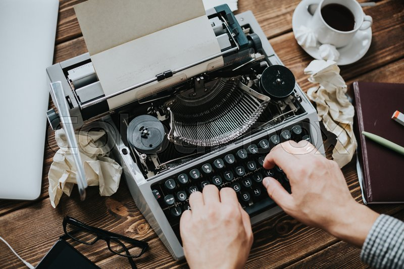Writer typing with retro writing machine. View from above, stock photo