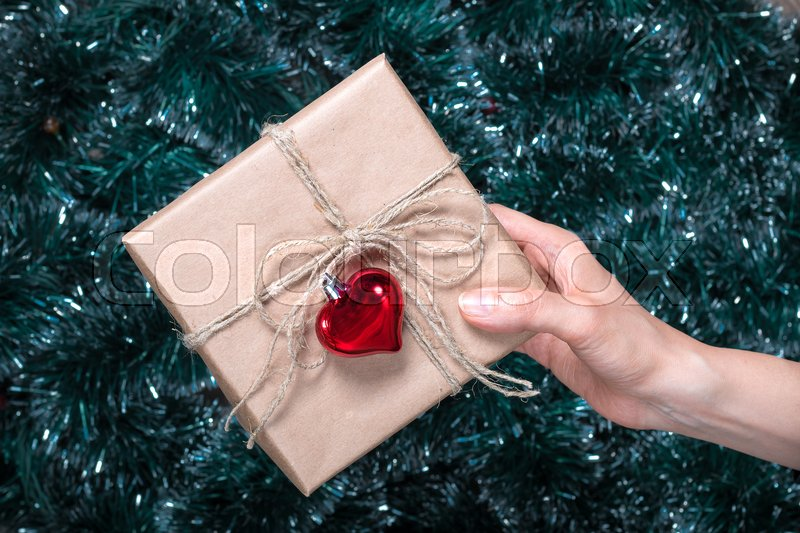 Packaging holiday gifts.Young girl packs a Christmas gift with Christmas decorations. Top view, stock photo