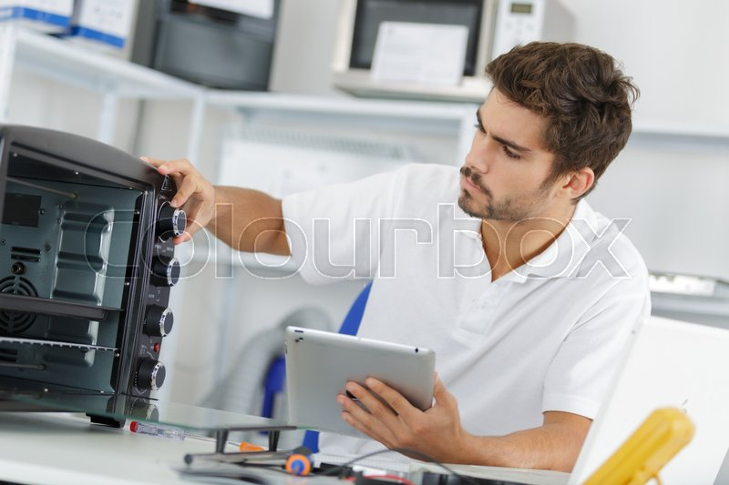 Attractive repairman concentrated at work, stock photo
