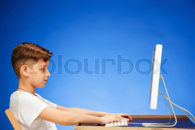 School-age boy sitting in front of the monitor laptop at blue studio backgroubd, stock photo