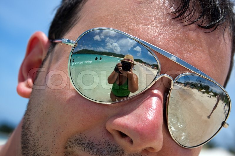d2ef4787f8 Close up of a man wearing reflective sunglasses in a tropical beach with  reflection of the woman photographer in the lens Shallow depth of field