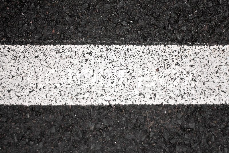 closeup of a tar or asphalt pavement texture with a white line painted