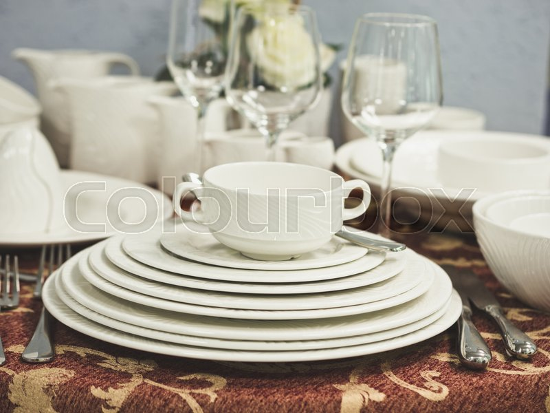 Set of new dishes on table with tablecloth. Stack of white plates and wine glasses with flowers on restaurant table. Shallow DOF, stock photo