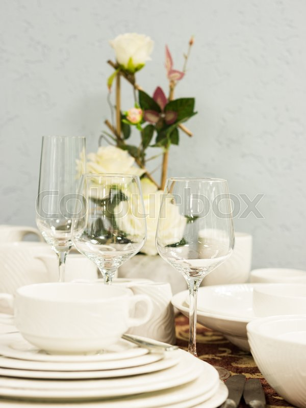 Set of new dishes on table with tablecloth. Stack of white plates and wine glasses with flowers on restaurant table. Vertical. Shallow DOF, stock photo