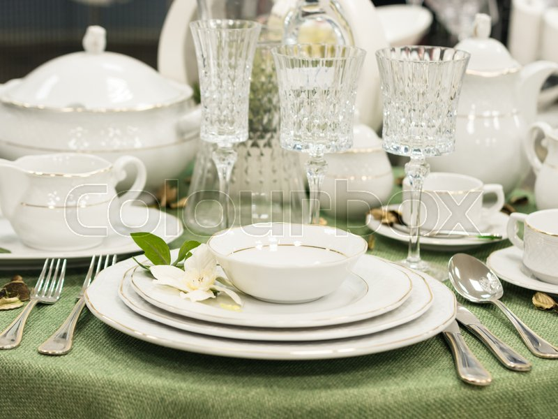 Set of new dishes on table with green tablecloth. Stack of white plates with flowers on restaurant table. Shallow DOF, stock photo