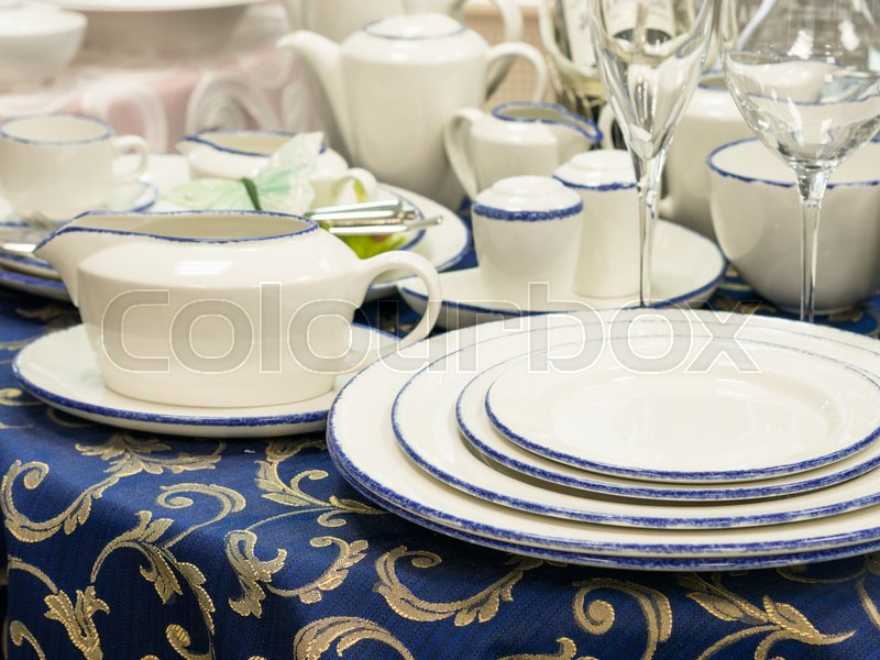 Set of new dishes on table with blue tablecloth. Stack of plates, saucer and wine glasses on restaurant table. Shallow DOF, stock photo