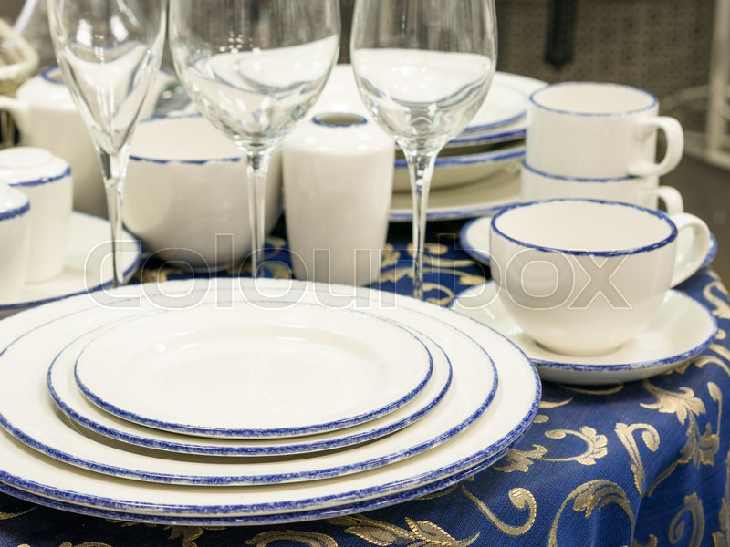 Set of dishes close up on table with blue tablecloth. Stack of plates, wine glasses and cups on restaurant table. Shallow DOF, stock photo