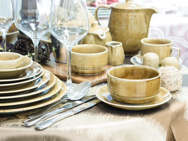 Set of new dishes on table with tablecloth. Stack of beige plates and wine glasses on restaurant table. Shallow DOF, stock photo