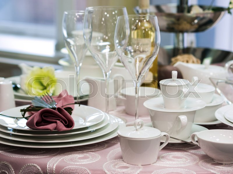 Set of new dishes on table with tablecloth. Stack of white plates and wine glasses on restaurant table. Shallow DOF, stock photo