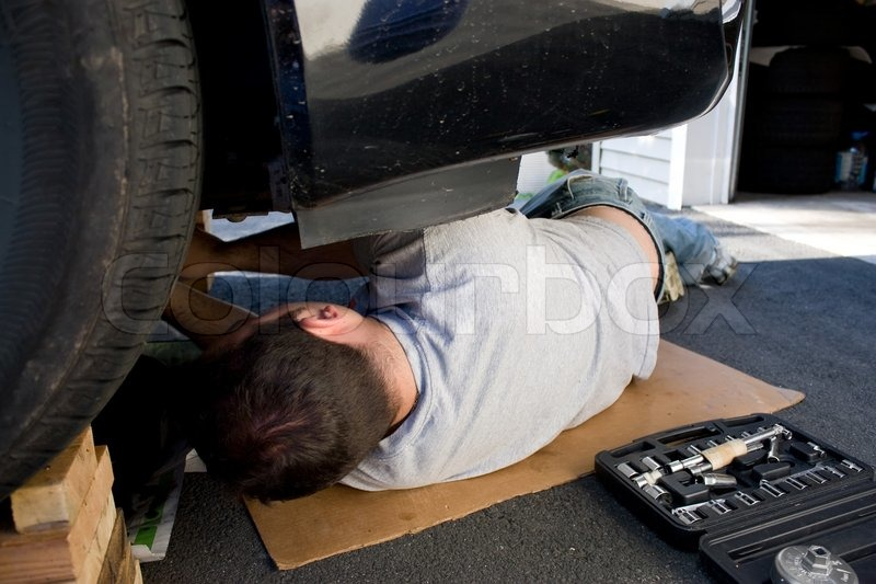 a young man laying underneath a car doing repairs or