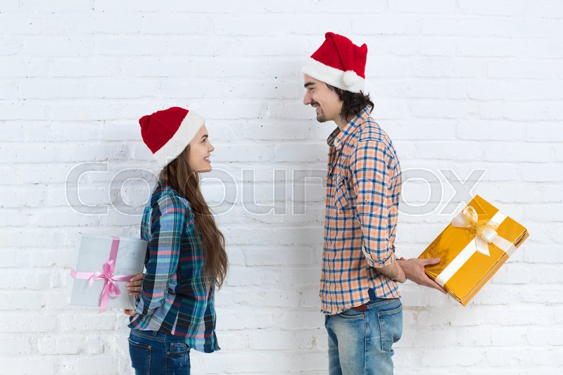 Christmas Holiday Happy Couple Hold Surprise Present Boxes Wear New Year Santa Hat Cap, Man And Woman Smiling Over White Brick Wall, stock photo