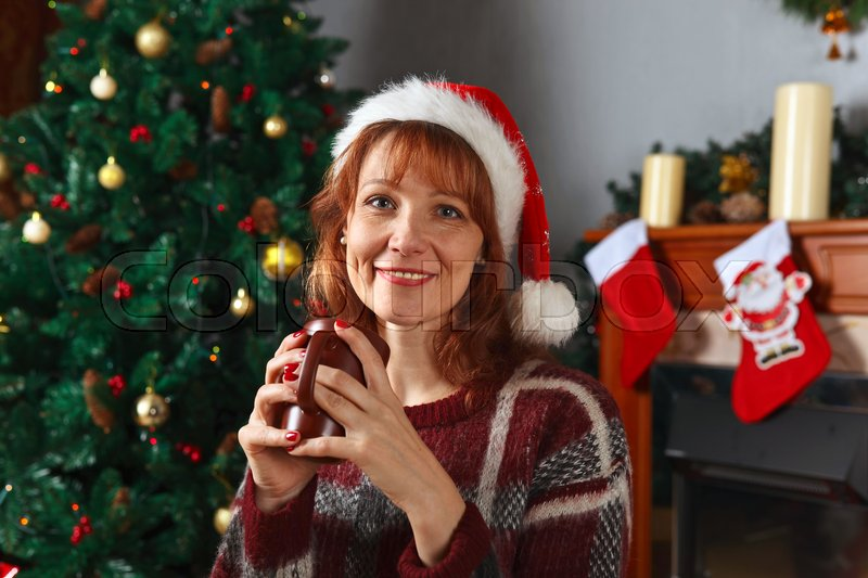 Woman with mug in the room with fireplace and Christmas decorations, stock photo