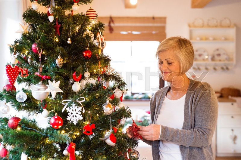 Beautiful senior woman decorating Christmas tree inside in her house, stock photo