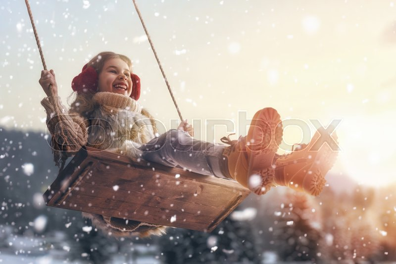 Happy child girl on swing in sunset winter. Little kid playing on a winter walk in nature, stock photo