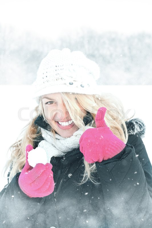 Winter happy woman in snow holding snow ball in hand for snowballing with thumb up outside on sunny cold winter vintage day. Portrait of smiling female model with pink gloves and white hat with scarf in first snow, stock photo