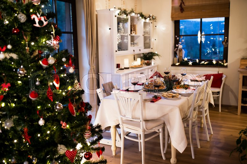 Christmas meal laid on table in decorated dining room. Roasted turkey or chicken, cookies, Christmas tree, plates and glasses of red wine, stock photo
