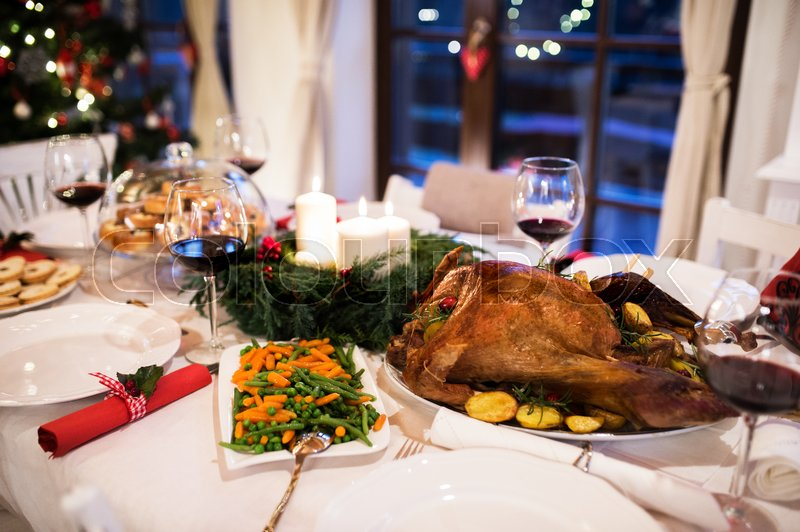 Christmas meal laid on table in decorated dining room. Roasted turkey or chicken, vegetables, cookies, Christmas wreath, glasses of red wine, stock photo