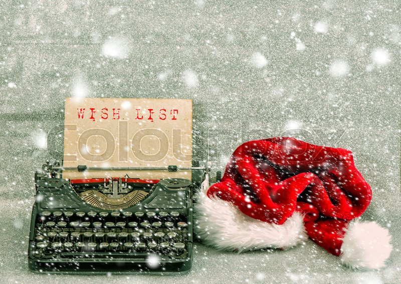 Old typewriter with red hat and sample text Wish List. Retro style picture with falling snow effect, stock photo