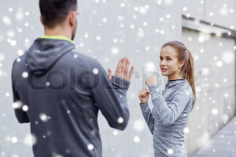 Fitness, sport, martial arts, self-defense and people concept - happy woman with personal trainer working out strike outdoors over snow, stock photo