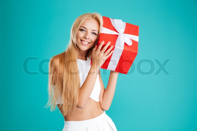Portrait of a happy wondered woman holding gift box isolated on the blue background, stock photo