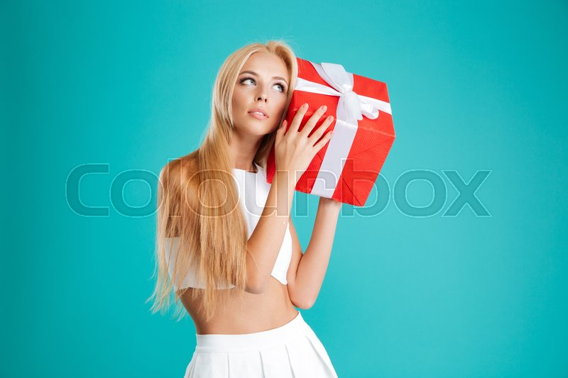 Portrait of a charming wondering woman holding gift box at her ear over blue background, stock photo