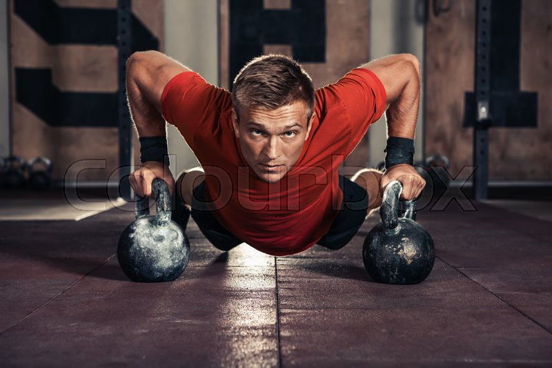 Handsome muscular man doing push ups on kettle ball in gym, stock photo