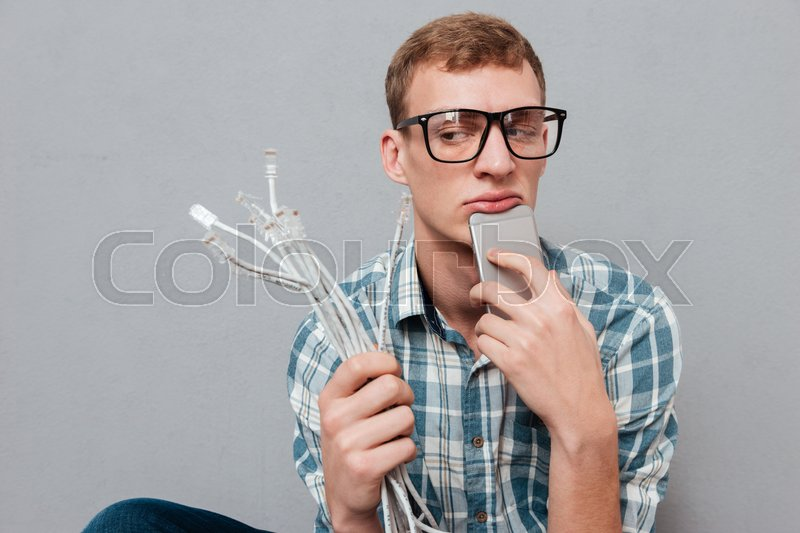 Hipster in glasses with phone and cables. looking away. isolated gray background, stock photo