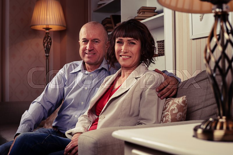 A mid shot a pair of sweethearts sitting on the couch and having their photo taken.A male wearing blue shirt and dark jeans embracing his lady, stock photo