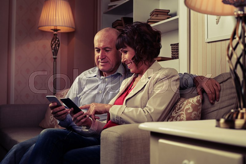 A mid shot of a pair communicating with one another, smiling and pointing at something funny on their mobiles. Elderly man and woman sitting in a room with an excellent modern interior, stock photo