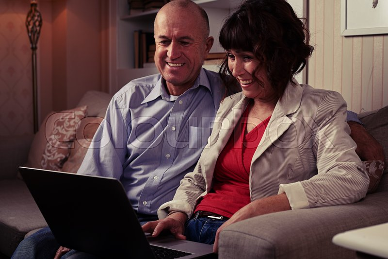 Side mid shot of an elderly pair watching in laptop on the umber settee. Man and woman dressed mainly in classics, stock photo