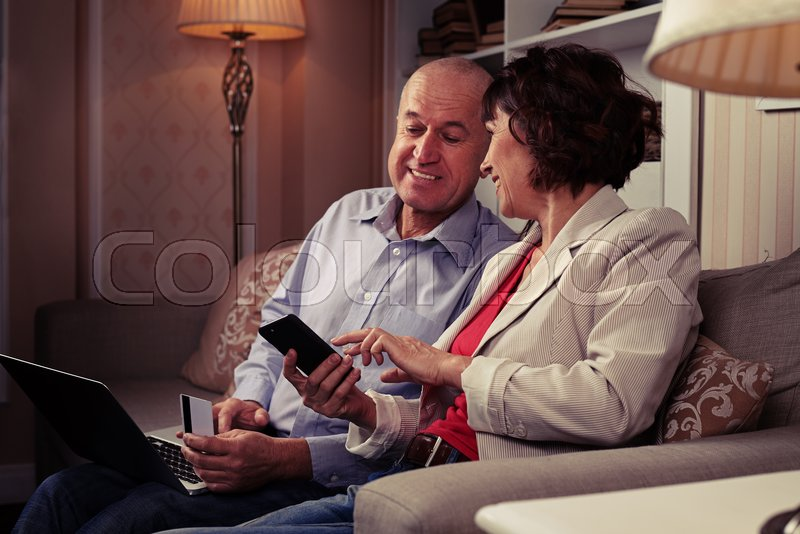 A mid shot of a smiling pair looking at something funny on the phone. People sitting on the settee with cute cushions, a laptop on man's knees, stock photo