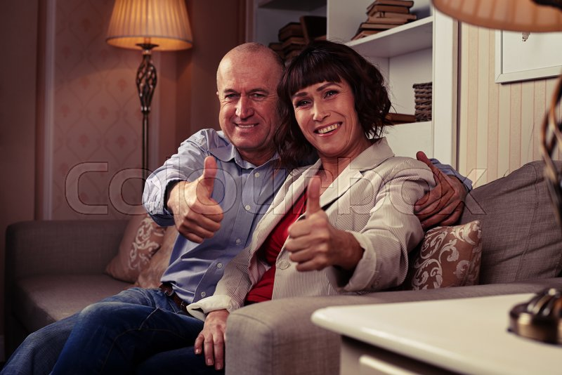 A mid short of two cute people showing their thumbs-up, demonstrating harmony and happiness, loving each other. Individuals wearing mainly classic clothes, stock photo
