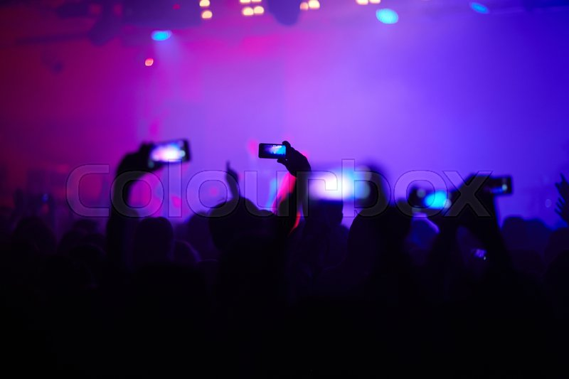 Hands of young people with smartphones recording pop concert, stock photo
