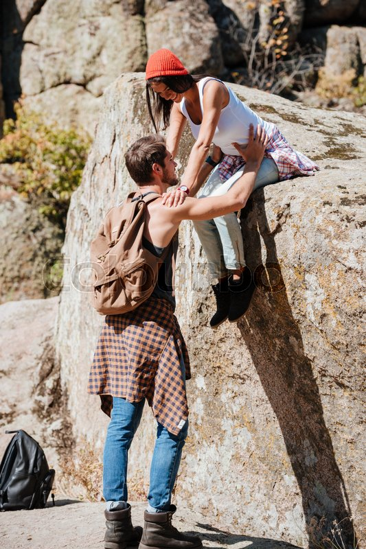 Man and woman teamwork climbing or hiking in summer, stock photo