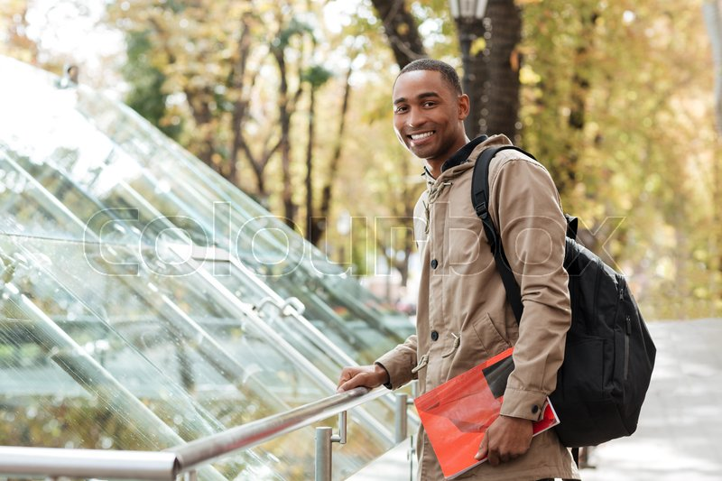 Image of young african cheerful man wearing backpack standing in the street while holding book and look at camera, stock photo