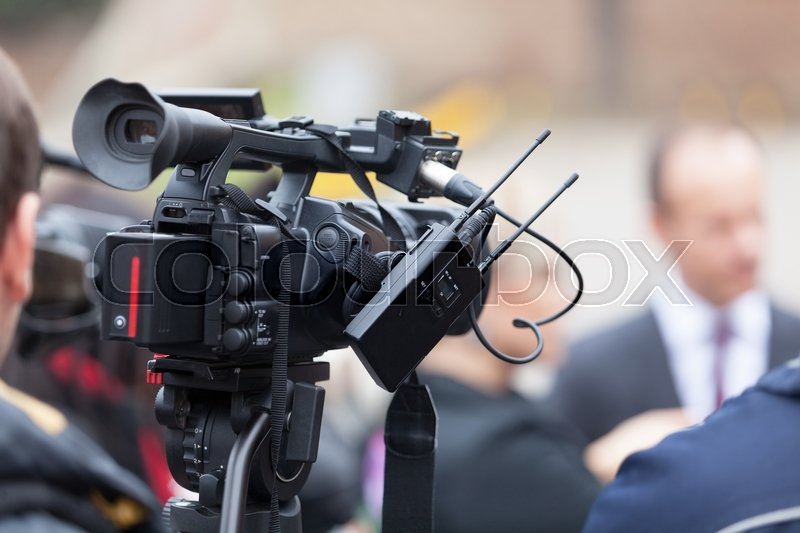 Filming an media event with a video camera. Press conference, stock photo