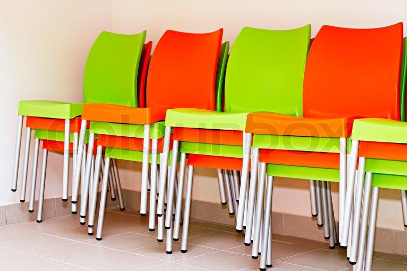 bunte st hle f r die besucher gestapelt aufeinander auf. Black Bedroom Furniture Sets. Home Design Ideas