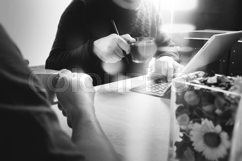 Office coffee break with two designer colleagues sitting chatting over cups of coffee,flower vase,digital tablet docking smart keyboard on marble desk,filters effect film, stock photo