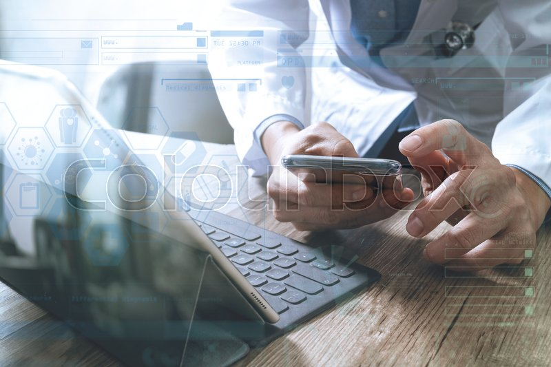 Smart medical doctor hand working with smart phone,digital tablet computer,stethoscope eyeglass,on wood desk,icons graphic screen effect, stock photo