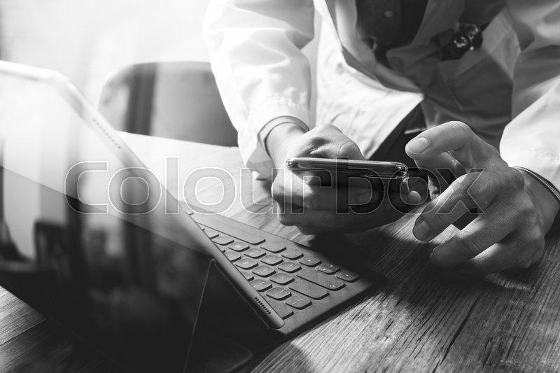 Smart medical doctor hand working with smart phone,digital tablet computer,stethoscope eyeglass,on wood desk,black white, stock photo
