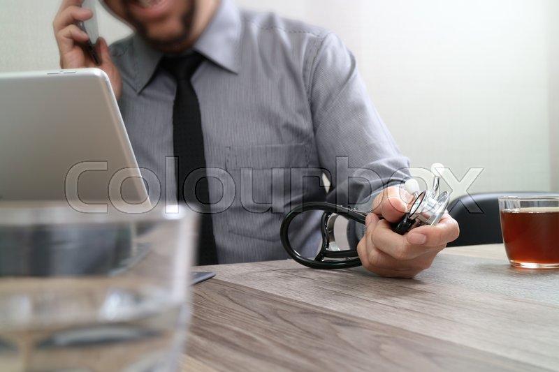 Smart medical doctor hand working with smart phone,digital tablet computer,stethoscope eyeglass,on wood desk, stock photo