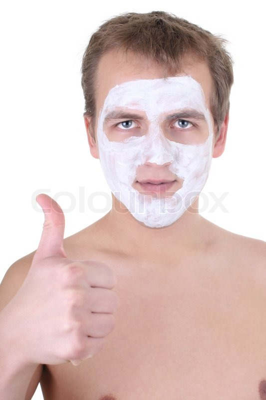 Stock image of 'Young man with cosmetic mask on his face thumbs up over  white