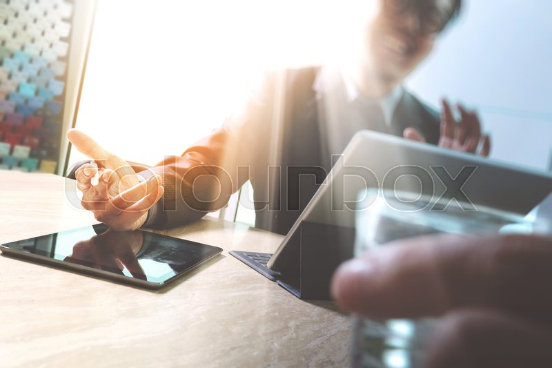 Business team meeting present. Happy professional investor working with new start up project. Digital tablet laptop computer design smart phone using, keyboard docking screen,sun flare, stock photo