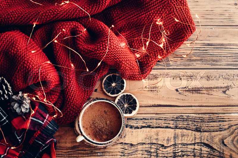 Stock image of 'Winter homely scene. Warm knit blanket and cup of hot cocoa, led lights string. Christmas holiday decor.'