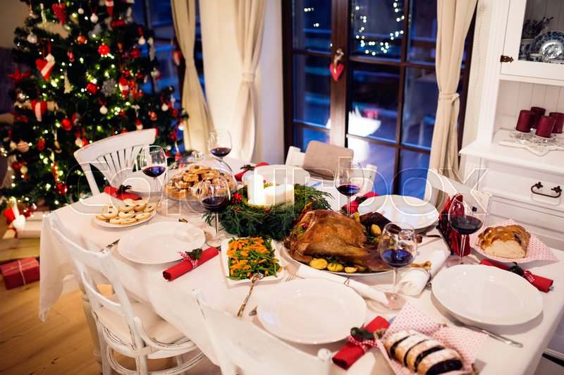 Christmas meal laid on table in decorated dining room. Roasted turkey or chicken, vegetables, cookies, Christmas tree, plates and glasses of red wine, stock photo
