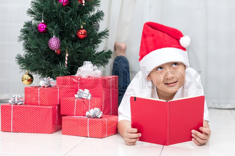 Happy Asian Chinese little boy reading book beside Christmas presents in the living room at home, stock photo