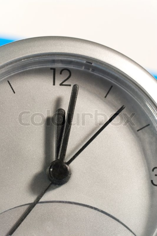 Closeup of a clock face (on a blue and white background), stock photo