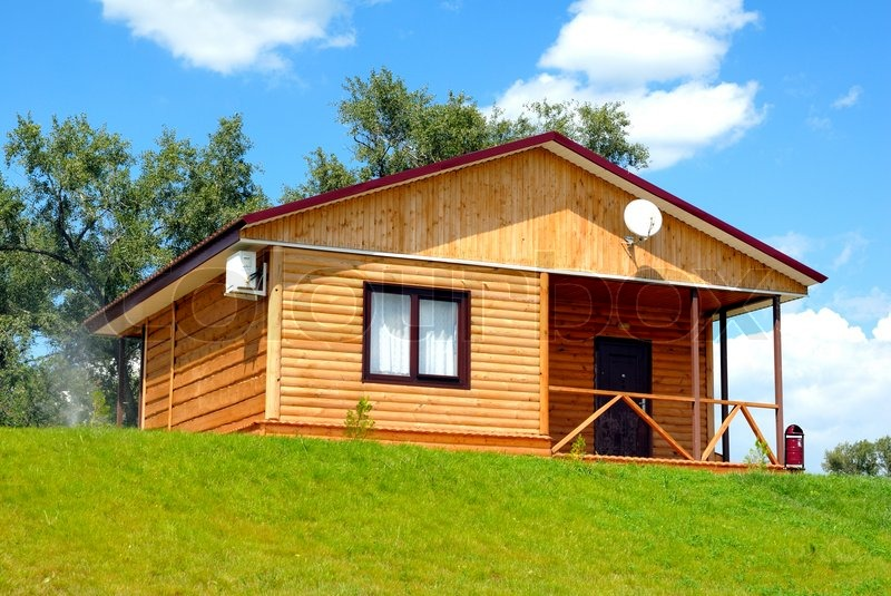The Wooden House With A Lawn On A Stock Photo
